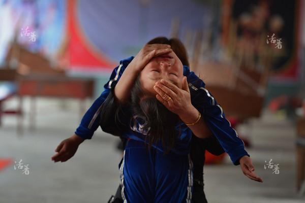 Bé gái bật khóc vì quá đau đớn khi bị cô giáo nắn người cho đúng động tác.