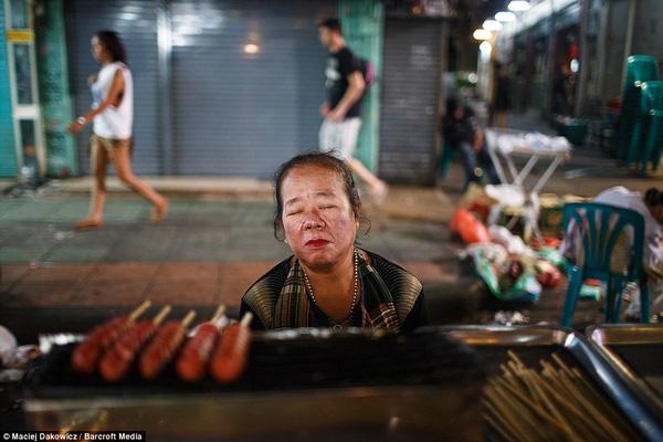Một người phụ nữ bán hàng vỉa hè mệt mỏi nhắm nghiền mắt lại sau một buổi tối bận rộn.