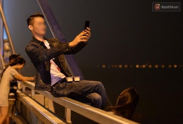Chụp ảnh tự sướng trên lan can cầu.