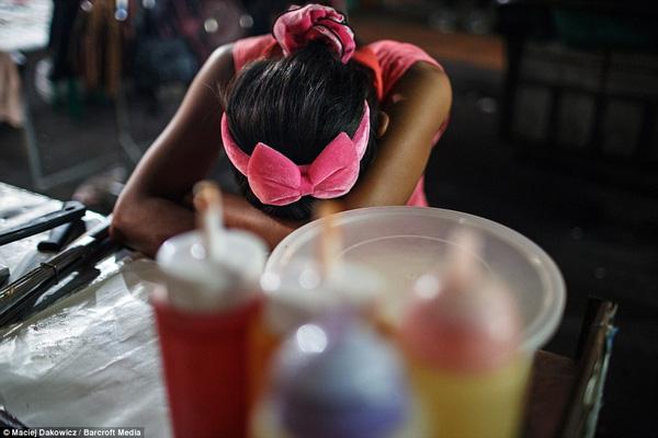 Một cô gái trên người mặc toàn màu hồng mệt mỏi gục xuống bàn sau một cuộc chơi thác loạn.