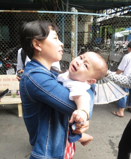 Cậu bé nghịch ngợm trong tay chị Nguyễn Thị Kim Quanh, cũng là một người dì. Chị Quanh là người đã một mình theo chuyến xe cấp cứu đưa Huy từ BV Hạnh Phúc (An Giang) lên TP HCM, khi cha bé cũng phải đi cấp cứu. Chị cũng là một trong những người luôn bên bé những chông chênh đầu đời.