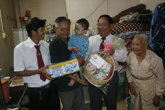 Ông Tạ Long Hỷ (thứ hai từ phải sang), Phó tổng giám đốc Vinasun, tặng quà Tết cho gia đình ông Mai Thành Liêm