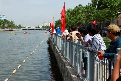 Người dân hai bờ kênh theo dõi vào dùng điện thoại ghi lại cảnh đua thuyền