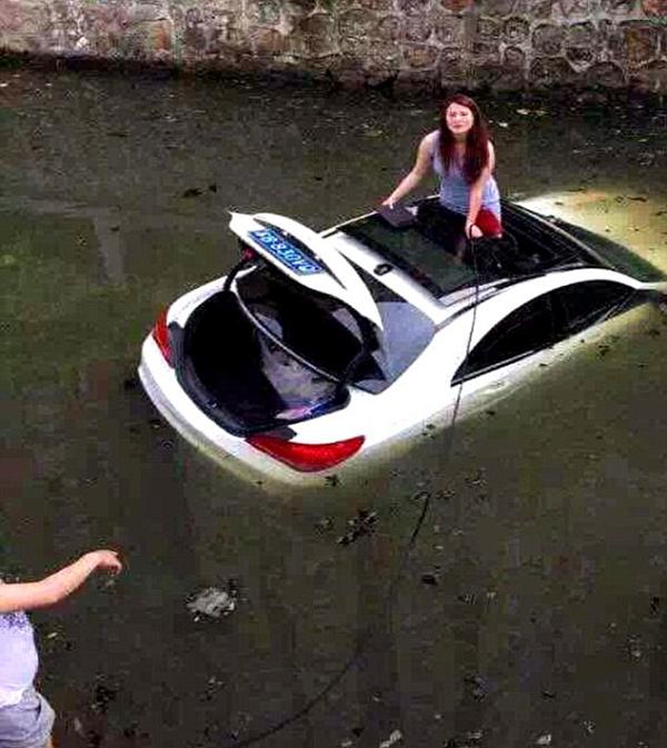 Người lái xe bám vào sợi dây thừng trong khi những người trên bờ sông cố gắng giúp đỡ cô.