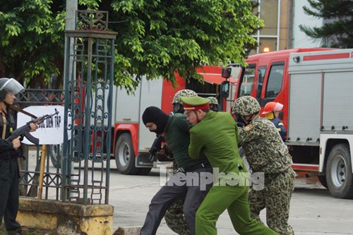 Áp giải các đối tượng trong nhóm khủng bố bị lực lượng đặc công đánh bắt trong nhà thi đấu.