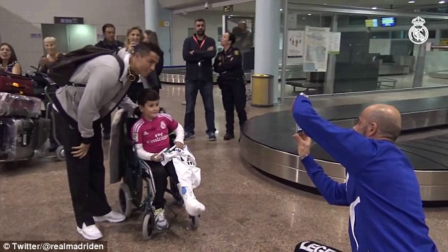 Ronaldo chụp ảnh với 1 fan nhí đi xe lăn.