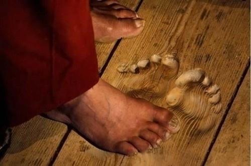 Bàn chân thật và dấu lòng bàn chân in trên sàn gỗ của lạt-ma Hua Chi vì luôn luôn cầu nguyện tại cùng một vị trí, nên chính lòng đôi bàn chân của ông đã ăn sâu xuống sàn gỗ.