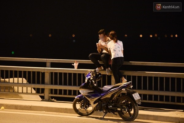 Ngồi chênh vênh trên thành cầu và thản nhiên cắm mặt vào... điện thoại.