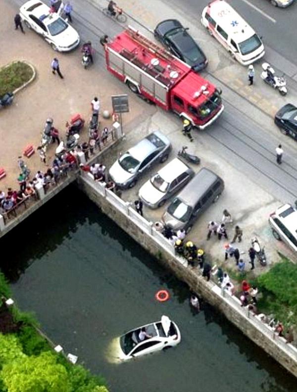 Người phụ nữ trèo qua cửa mái ô tô đang được lính cứu hỏa cứu thoát khỏi chiếc xe đang chìm dần xuống nước.