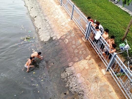 Nhiều người đứng ở hai bờ kênh Tàu Hủ - Bến Nghé cổ vũ