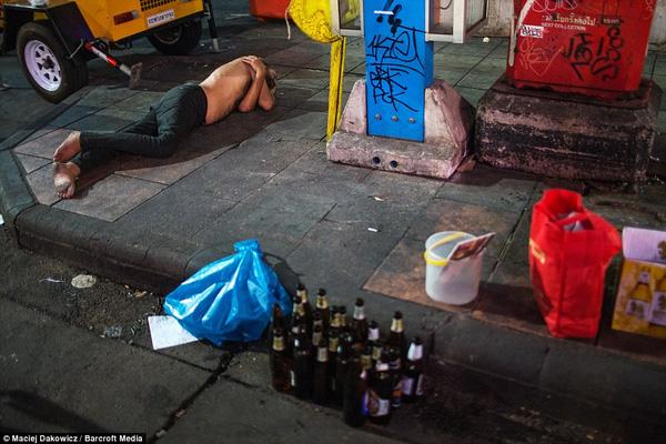 Một người đàn ông không có áo, không có giày nằm ngủ vạ vật trên vỉa hè, cạnh đó là chục vỏ chai bia bỏ không, xô và túi nhựa.