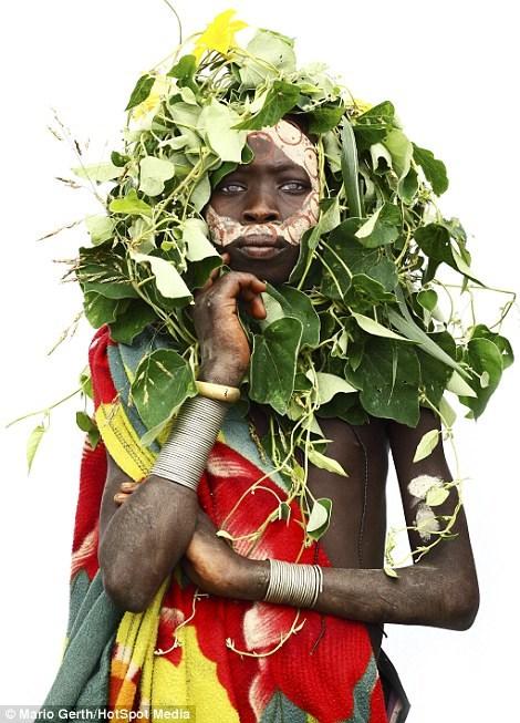 Các em bé của bộ lạc Surma từ Ethiopia đội chiếc mũ và mặt nạ làm từ cây cỏ và đất sét trắng. (Nguồn: Dailymail.co.uk)