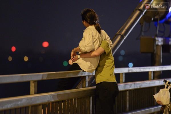 Vô tư ôm ấp nhau trên thành cầu.