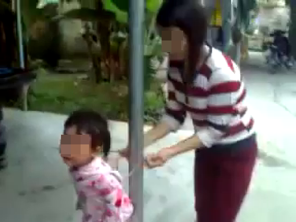 Khi dây trói tay bị cô bé giằng ra, người mẹ quyết định buộc lại để tiếp tục dạy bảo