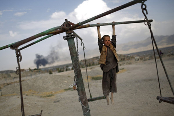 Cậu bé chơi đu quay trên một đỉnh đồi ở thành phố Kabul, Afghanistan.