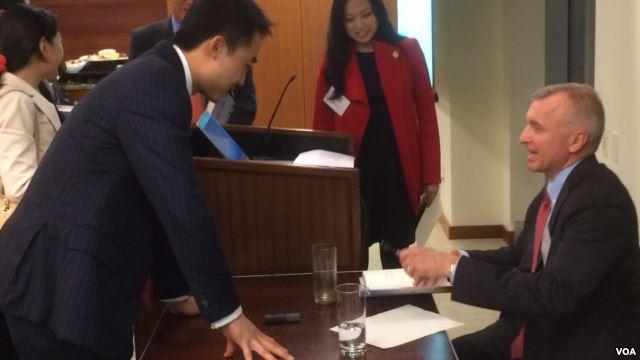 Bạc Qua Qua được cựu Phó trợ lý Ngoại trưởng Mỹ Thomas J. Christensen (phải) ký tặng lên sách. Ảnh: VOA