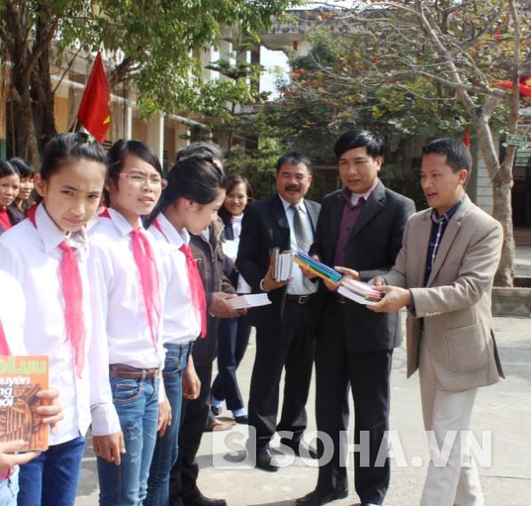 Đại diện lãnh đạo Báo, địa phương, nhà trường trao tặng sách cho các em học sinh.