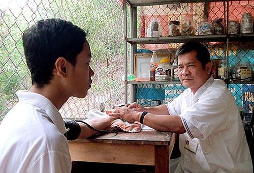 Lương y Đình Thuấn đang bắt mạch chữa bệnh cho bệnh nhân.