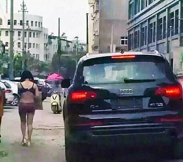 Wang Ni cúi mặt đi trên đường phố trong tình trạng chỉ mặc đồ lót, trong khi, người chồng lái xe ô tô ở phía sau để xem người vợ bị làm nhục.