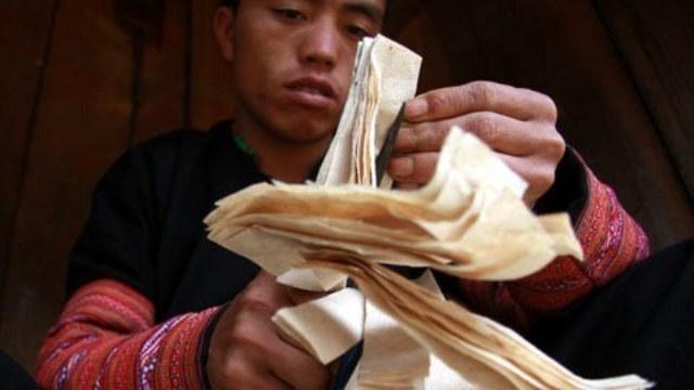 Người Mông cắt giấy trang trí bàn thờ và nhà cửa ngày Tết. (Ảnh: Vietnamnet)
