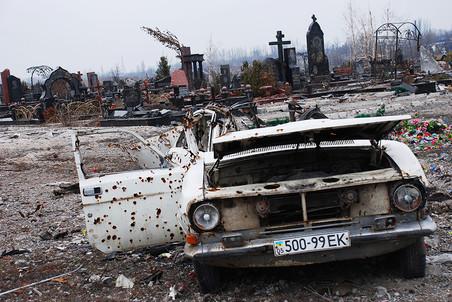 Chiếc xe ô tô bị phá hủy phía trước nghĩa trang cạnh sân bay Donetsk. Ảnh: Gazeta.ru