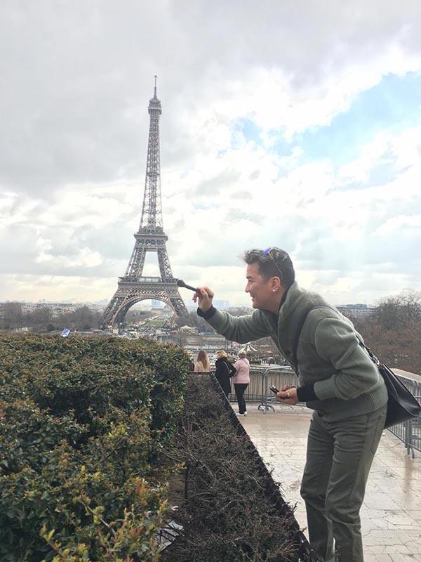 Hình ảnh Mr Đàm dùng cây cọ sơn để tạo dáng hài hước bên công trình nổi tiếng của Pháp.