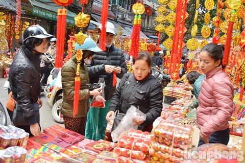 Tại phố Hàng Mã (Hà Nội), nhiều người dân tranh thủ mua bao lì xì, đồ trang trí,...