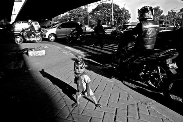 Chú khỉ đeo mặt nạ đang trình diễn trên đường phố Kampung Munyet.