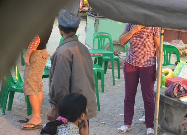 Bị PV truy vấn, người đàn ông này đứng dậy bỏ đi và nói chuyện với người quen đang bán hàng ngay cổng chùa, sau đó đi về phía trong làng.