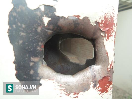 Một cánh cửa cổng bằng sắt ở căn nhà đối diện với hiện trường xảy ra vụ nổ bị một vật bằng kim loại từ vụ nổ bắn xuyên qua.