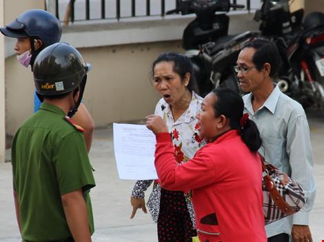 """Bà Hó đứng trong sân tòa giải thích với cảnh sát về lý do """"đại náo"""" tòa án- ảnh HÀM YÊN"""