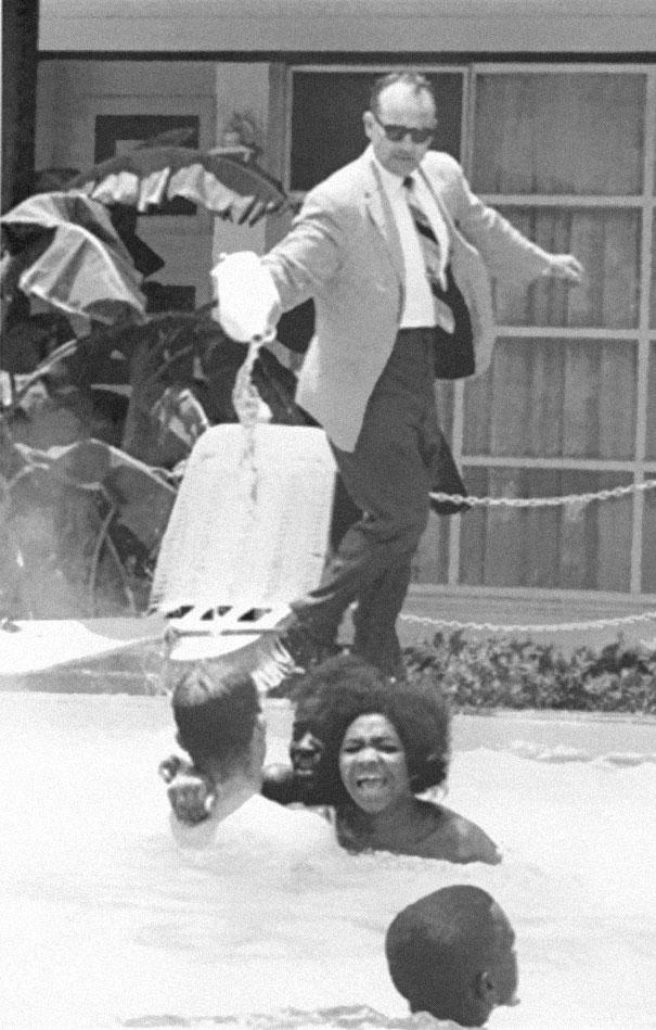 Bức ảnh ghi lại khoảnh khắc một người chủ khách sạn đổ axit vào hồ bơi khi có những người da đen bơi ở đó. Ảnh chụp năm 1964