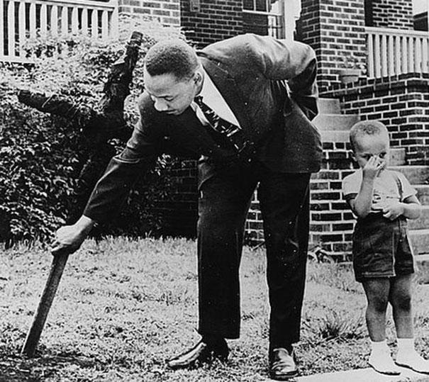 Martin Luther King cùng con trai đang dụi một thanh củi cháy trong khoảng sân trước nhà. Bức ảnh chụp năm 1960