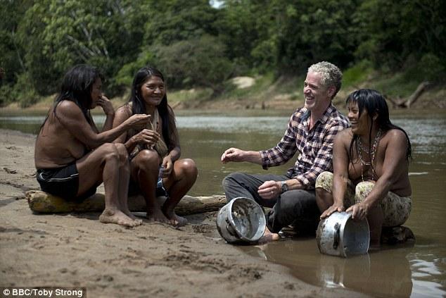 Gordon cùng những người phụ nữ thổ dân cọ rửa xoong nồi và cùng bàn luận về loài trăn khổng lồ nguy hiểm.