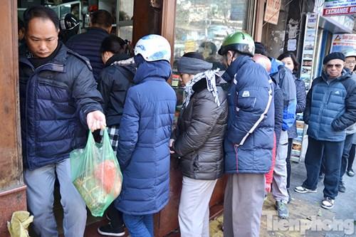Tại một cửa hàng bánh chưng, giò chả trên phố Hàng Bông, nhiều người xếp thành hàng dài.