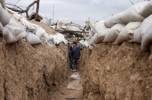 Chiến binh phiến quân Syria di chuyển dọc đường hào tại thị trấn Jobar.