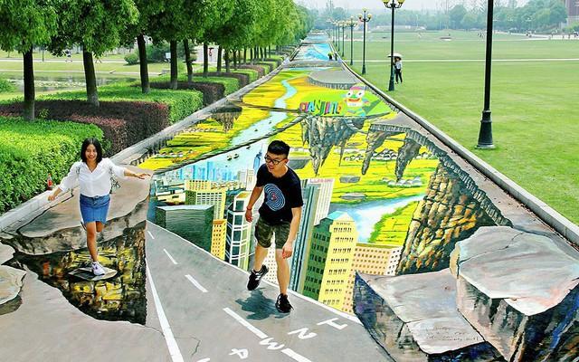 Sinh viên chụp ảnh với những bức tranh 3D dọc một con đường trong trường đại học Nam Kinh, tỉnh Giang Tô, Trung Quốc.