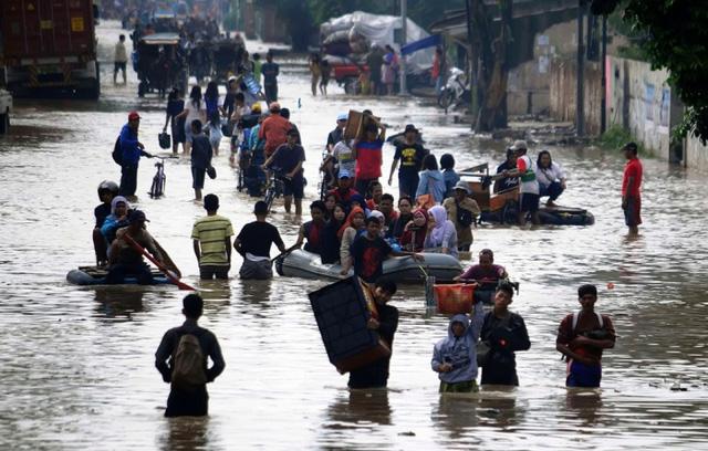Người dân lội trên đường phố ngập lụt ở Bandung, Indonesia.