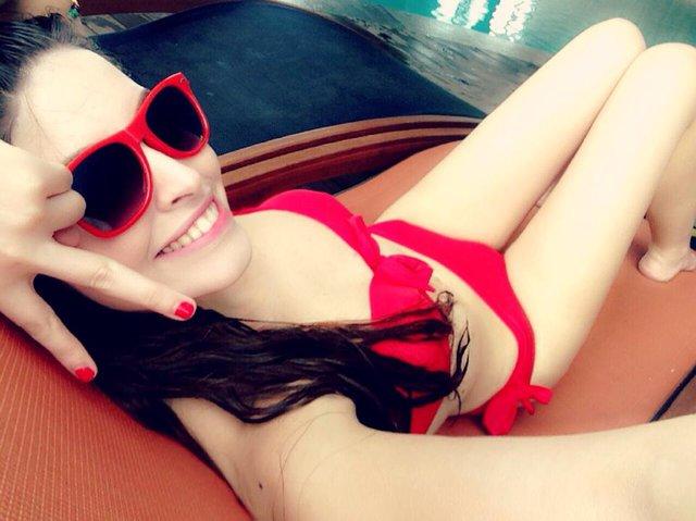 Andrea nổi bật với bộ kinini đỏ xuyệt tông với kính mắt và màu móng