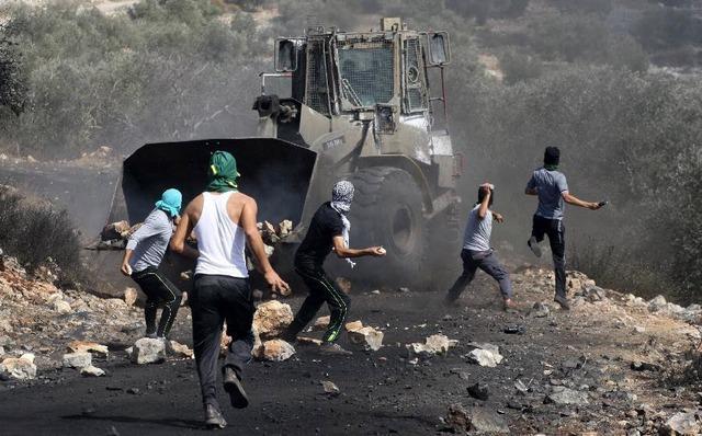 Người Palestine ném đá vào binh sĩ Israel trong cuộc biểu tình phải đối khu định cư của người Do Thái ở ngôi làng Kufr Qadoom gần thành phố Nablus, Bờ Tây.