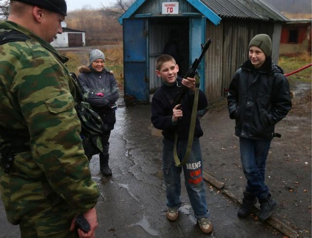 Cậu bé cầm súng đứng bên ngoài một hầm tránh bom ở thành phố Donetsk, Ukraine.