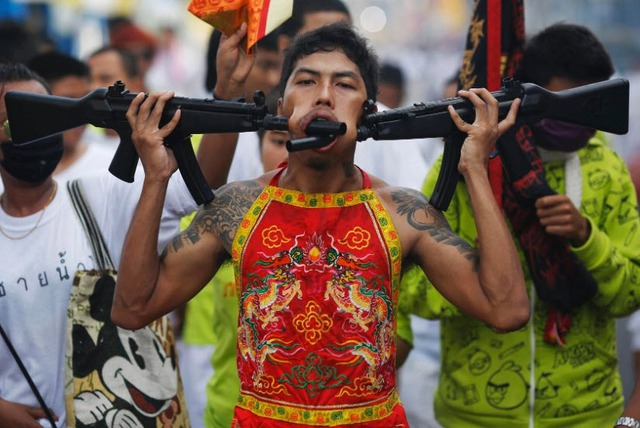 Người đàn ông biểu diễn xuyên các thanh sắt nhọn qua má và môi tại lễ hội ăn chay ở Phuket, Thái Lan.