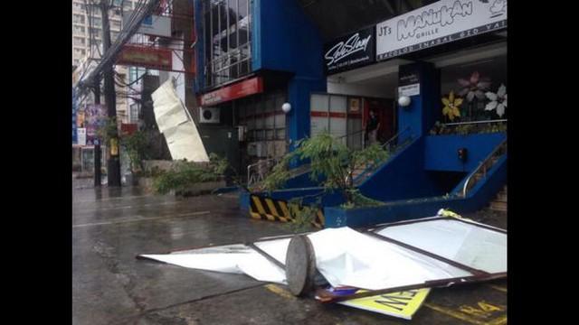 Gió bão thổi bay biển quảng cáo ở thành phố Quezon.