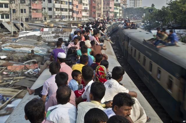 Những người theo đạo Hồi ngồi trên nóc đoàn tàu đông đúc tại Dhaka, Bangladesh, để trở về quê trong dịp lễ Eid al-Adha.