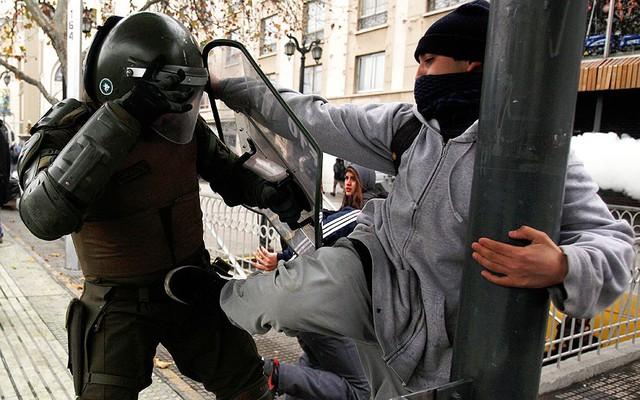 Một sinh viên đá cảnh sát chống bạo động trong cuộc biểu tình ở Santiago, Chile.