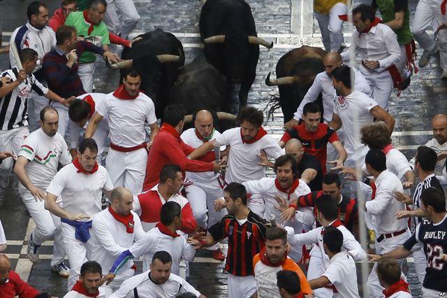 Mọi người chạy đua với bò tại lễ hội bò rượt San Fermin tại thành phố Pamplona, Tây Ban Nha.