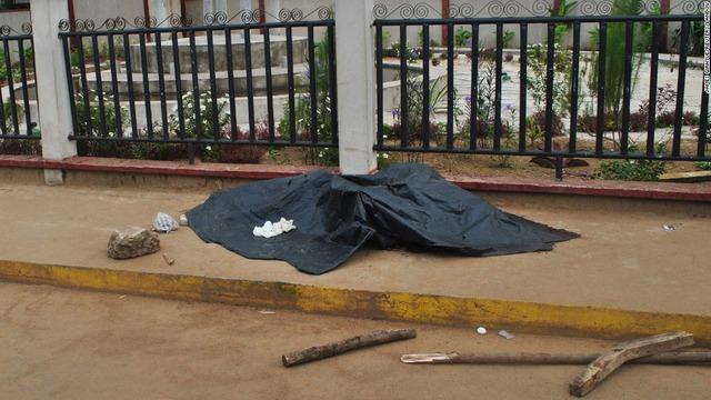 Thi thể một người đàn ông được che bằng vải dầu trước khi được xét nghiệm virus Ebola ở Monrovia, Liberia.