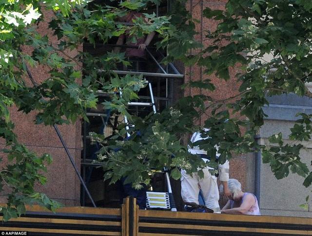 Cảnh sát trèo qua cửa số tầng 1, phía trên quán cafe để sơ tán những người ở bên trong toà nhà.