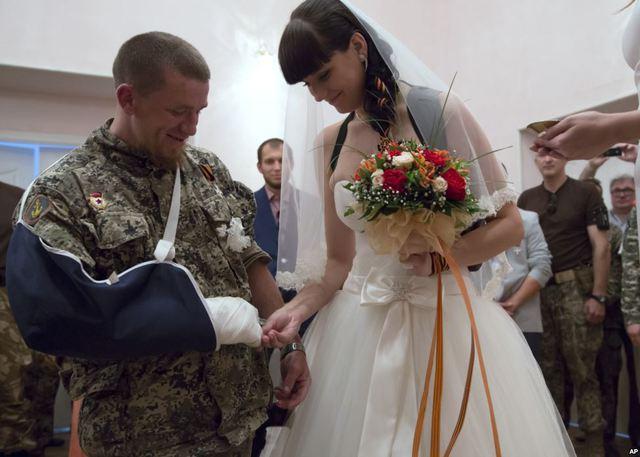 Một binh sĩ bị thương của lực lượng tự vệ Cộng hòa nhân dân Donetsk và cô dâu trao nhẫn cho nhau trong lễ cưới của họ tại thành phố Donetsk, miền đông Ukraine.