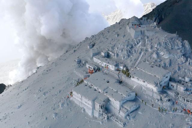 Các thành viên của Lực lượng phòng vệ Nhật Bản thực hiện hoạt động cứu hộ tại khu nhà nghỉ trên núi bao phủ đầy tro bụi phun trào từ núi lửa Ontake.
